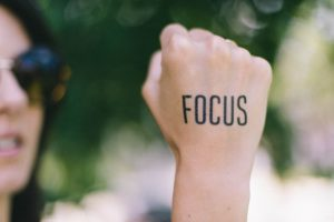 "A woman's fist on which is written the word ""focus"""