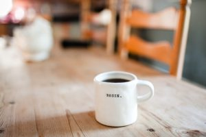 "White ceramic mug with ""begin"" written on it."