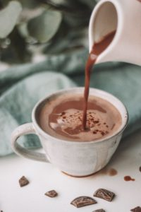 Hot chocolate pouring in a white mug.