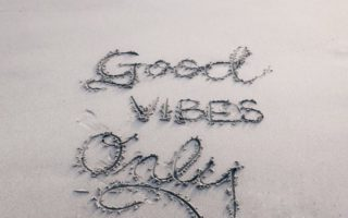 """good vibes only"" written on a beach"