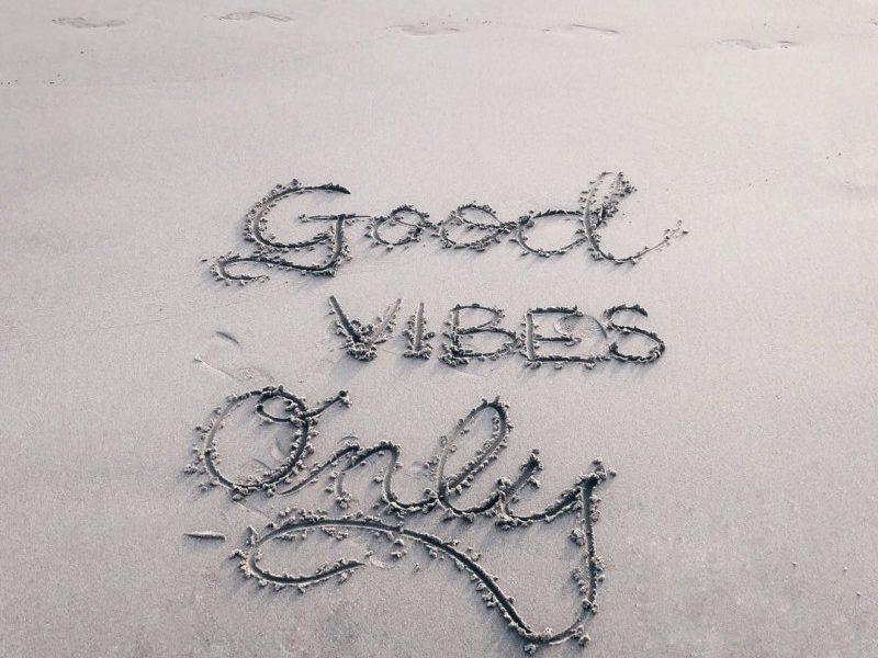 """good vibes only"" written on a beach"