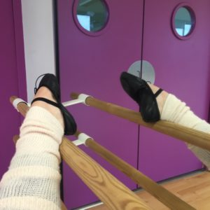A leg stretching at the barre.