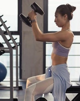 Compound exercise. A woman is doing a shoulder press.