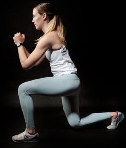 A woman doing a front lunge compound exercise
