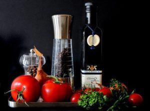 A bottle of extra-virgin olive oil and tomatoes