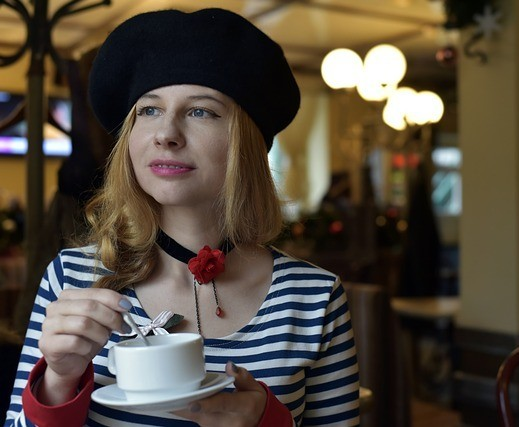 A French woman sipping a coffee at a cafe