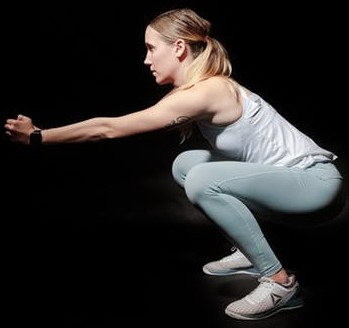 Compound exercise. A woman is squatting.