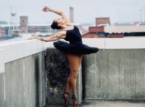 A ballerina with a tatoo in a black tutu