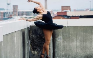 A ballerina with a tatoo in a black tutu