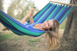 Rest days-Cheerful young woman resting in colorful hammock