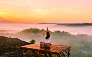 rest days-woman doing yoga watching sunset
