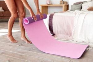 Immunity boost-woman unrolling yoga mat before exercise