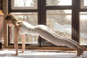 benefits doing planks-a woman doing the plank pose on a yoga mat